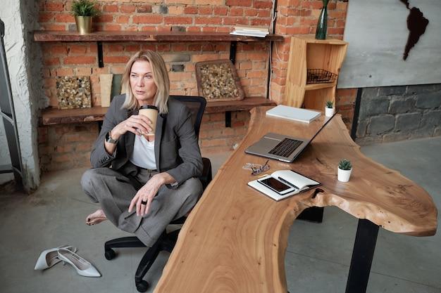 Mulher de negócios madura pensativa, sentada com as pernas cruzadas na cadeira do escritório e bebendo café, enquanto reflete sobre o projeto