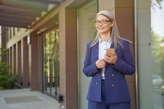 Mulher de negócios maduro atraente feliz em terno clássico usando smartphone e sorrindo em pé contra o prédio de escritórios ao ar livre. pessoas de negócio