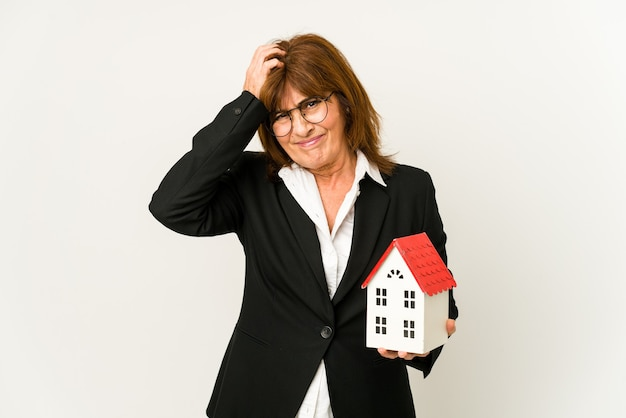 Mulher de negócios maduros segurando um modelo de casa