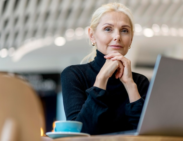 Mulher de negócios mais velha estoica posando enquanto trabalha e toma café