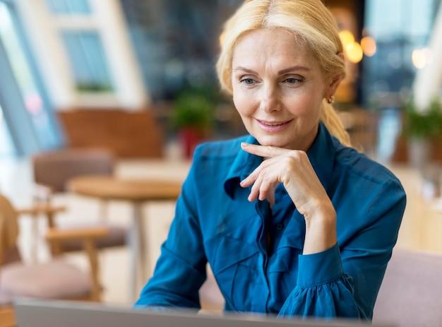 Mulher de negócios mais velha trabalhando em um laptop em uma lanchonete