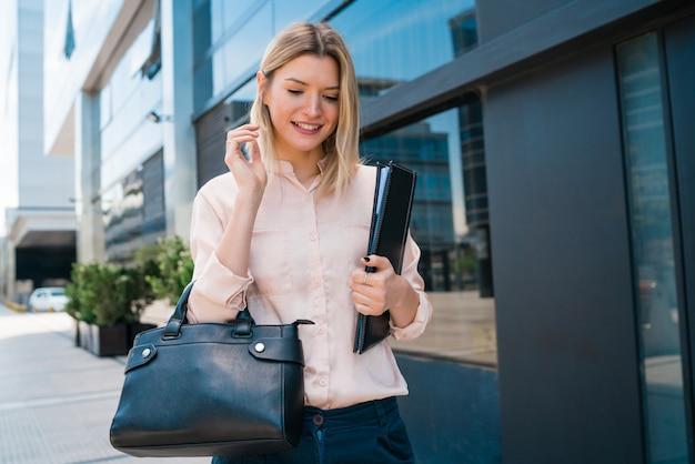 Mulher de negócios, mantendo a área de transferência e em pé ao ar livre