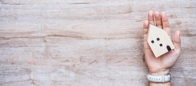 Mulher de negócios, mantendo o modelo de casa de madeira