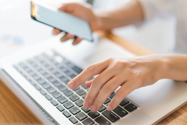 Mulher de negócios mão com gráficos financeiros e telefone celular sobre o laptop na mesa.