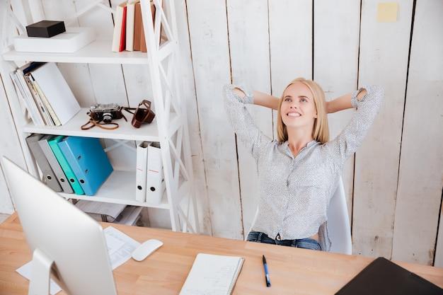 Mulher de negócios maravilhada sorridente, descansando enquanto está sentada na cadeira em seu local de trabalho