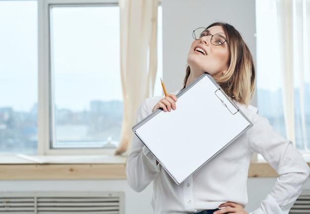 Mulher de negócios, mas estamos com uma folha de papel branca em uma sala iluminada