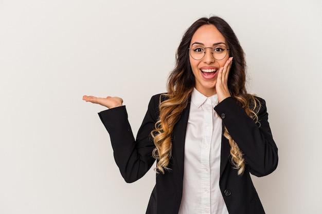 Mulher de negócios mexicanos jovem isolada no fundo branco mantém o espaço da cópia na palma da mão, mantenha a mão na bochecha. espantado e encantado.