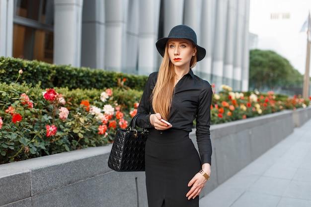 Mulher de negócios moderna com roupas elegantes andando perto do prédio com flores