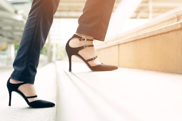 Mulher de negócios moderna trabalhando pernas closeup subindo as escadas
