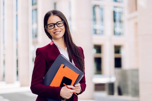 Mulher de negócios morena atraente de terno marrom e óculos, segurando o diário ee caderno grande estar de bom humor. conceito de pessoas de negócios.