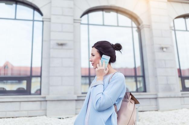 Mulher de negócios morena atraente falando no celular com o cliente no fundo de edifícios de escritórios