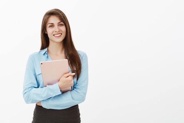 Mulher de negócios morena atraente positiva posando no estúdio