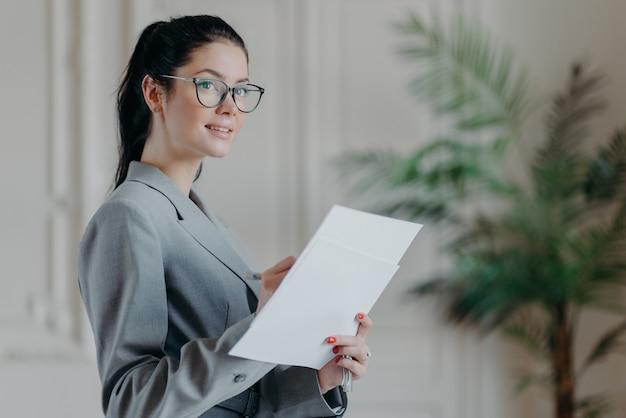 Mulher de negócios morena bem-sucedida fica pensativa com os documentos em papel