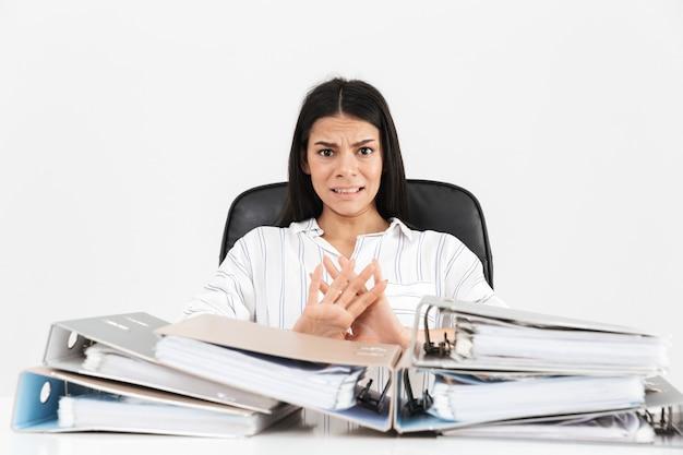 Mulher de negócios morena decepcionada trabalhando e sentada no escritório com um monte de pastas de papel na mesa isolada sobre a parede branca