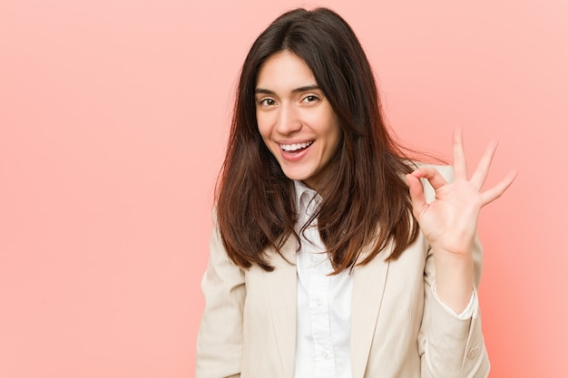 Mulher de negócios morena jovem contra um fundo rosa pisca um olho e mantém um gesto bem com a mão.