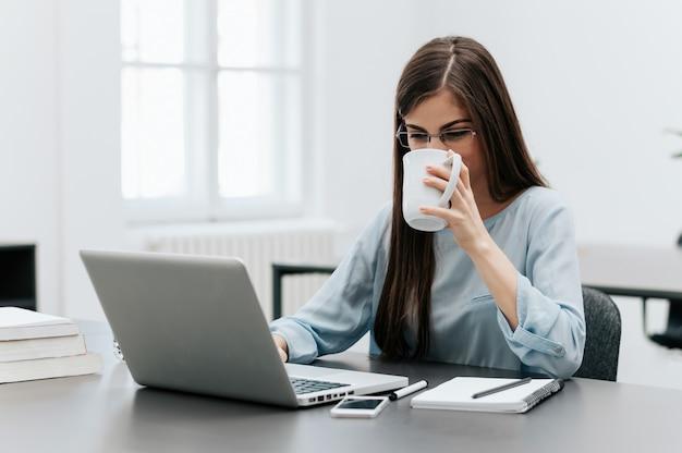 Mulher de negócios moreno atrativa que trabalha em no seu portátil e café bebendo em seu escritório.