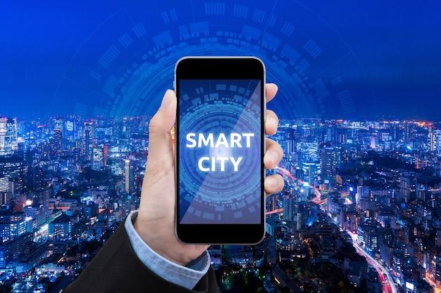 Mulher de negócios mostra tecnologia cidade inteligente no celular