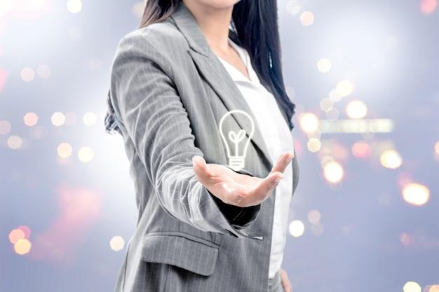 Mulher de negócios, mostrando a lâmpada brilhante nas mãos como um símbolo da ideia inovadora