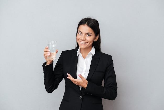 Mulher de negócios, mostrando o copo de água mineral na mão