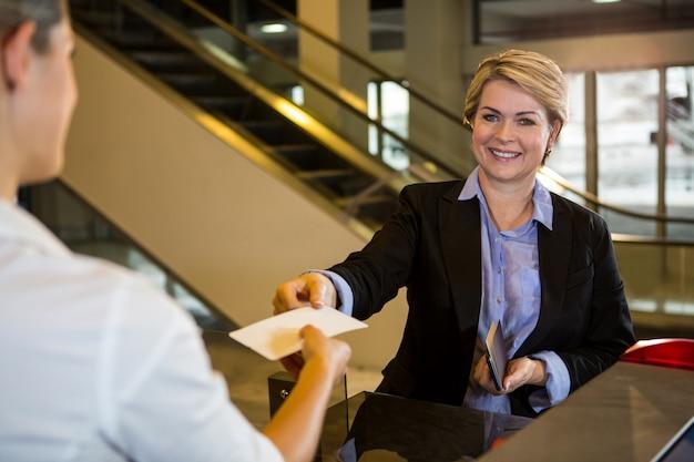 Mulher de negócios mostrando seu cartão de embarque no balcão de check-in