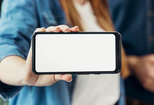 Mulher de negócios mostrando um telefone com tela vazia