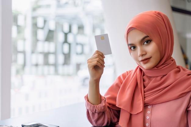 Mulher de negócios muçulmana asiática jovem bonita no hijab rosa e casual wear mãos mostrando um cartão de crédito branco