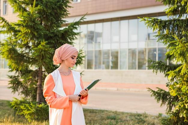 Mulher de negócios muçulmana asiática jovem sorrindo e segurando um documento de arquivo ao ar livre