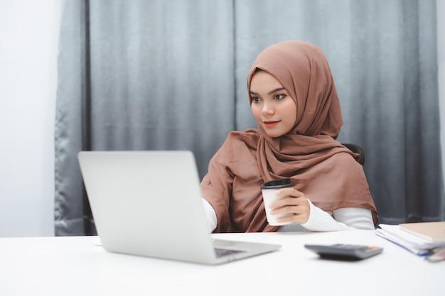 Mulher de negócios muçulmana asiática nova no vestuário desportivo esperto que senta e que trabalha com laptop em casa.