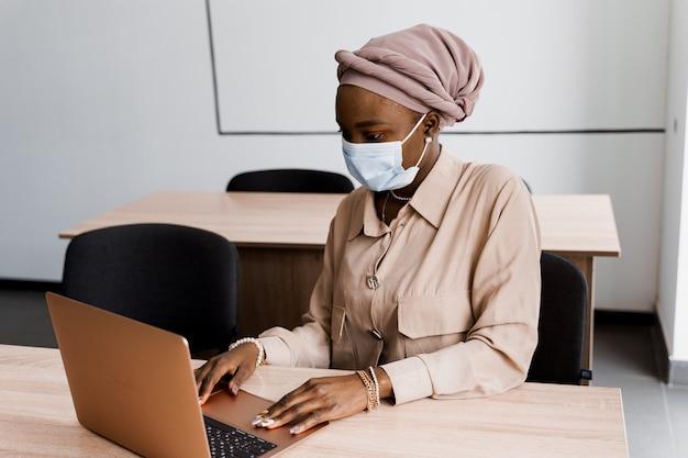 Mulher de negócios muçulmana negra na máscara médica com laptop.