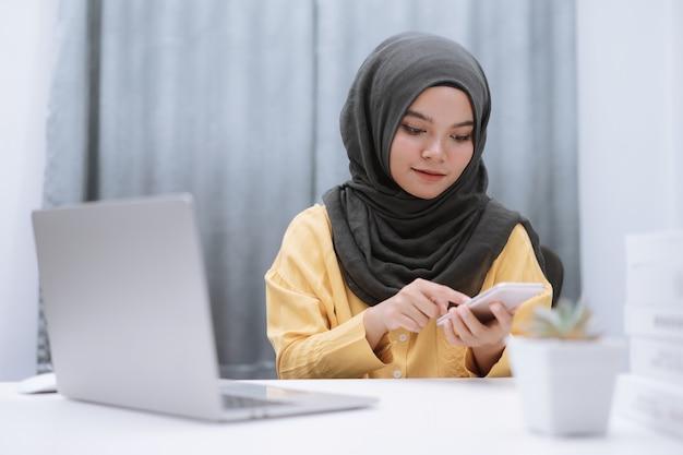 Mulher de negócios muçulmana trabalhando em casa com laptop e smartphone