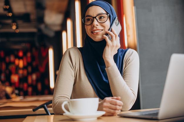 Mulher de negócios muçulmana trabalhando no computador em um café
