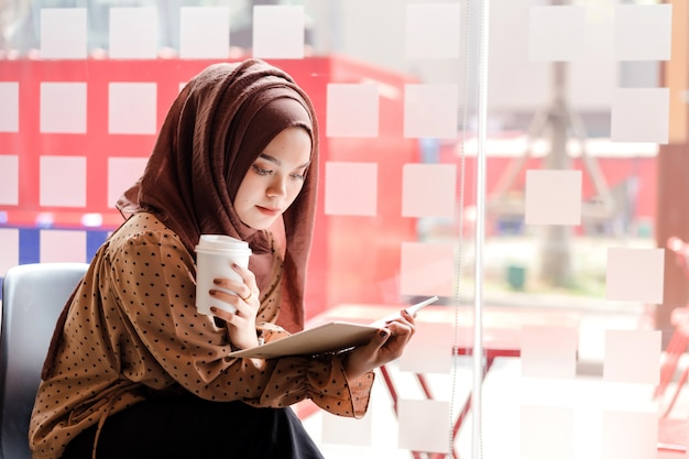 Mulher de negócios muçulmano asiáticos jovens na mão inteligente desgaste casual, segurando uma xícara de café