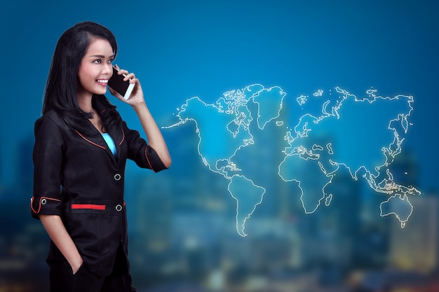Mulher de negócios muito asiática fala ao telefone com o cliente de negócios