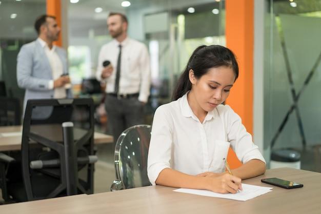 Mulher de negócios muito asiática focada escrevendo na mesa no escritório