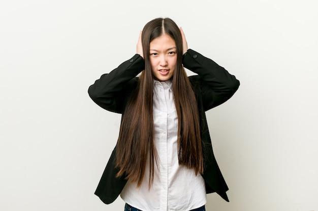 Mulher de negócios muito chinês jovem cobrindo os ouvidos com as mãos, tentando não ouvir som muito alto.
