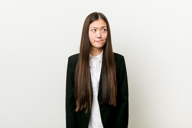 Mulher de negócios muito chinês jovem confusa, sente-se duvidoso e inseguro.