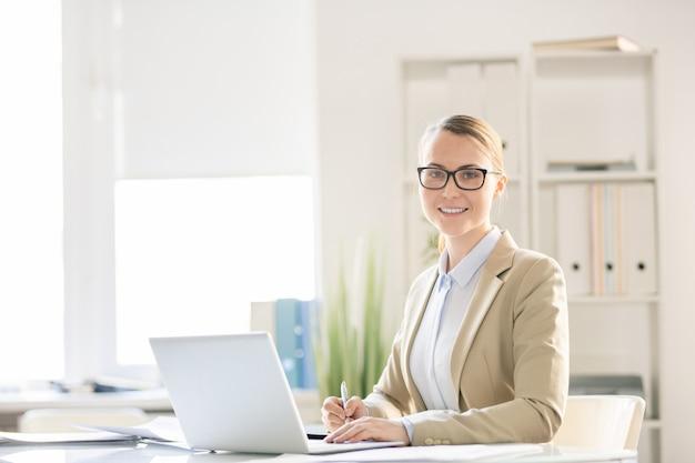 Mulher de negócios muito jovem e confiante sorridente em óculos, sentada à mesa com o laptop e fazendo anotações enquanto trabalhava no escritório