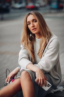 Mulher de negócios muito jovem elegante com telefone sentado, posando na rua. moda feminina, estilo casual e feminilidade. foto de alta qualidade