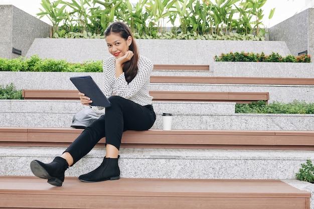 Mulher de negócios muito jovem sorridente, sentada em um banco de madeira com um tablet nas mãos e sorrindo na frente