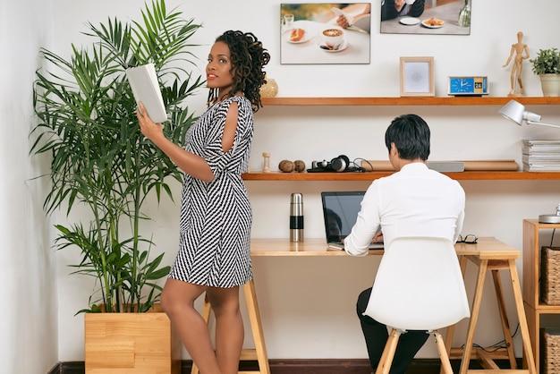 Mulher de negócios muito negra lendo anotações em seu planejador quando um colega está trabalhando em um laptop na mesa do escritório