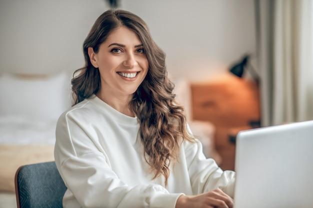 Mulher de negócios. mulher jovem elegante sentada à mesa trabalhando em um laptop