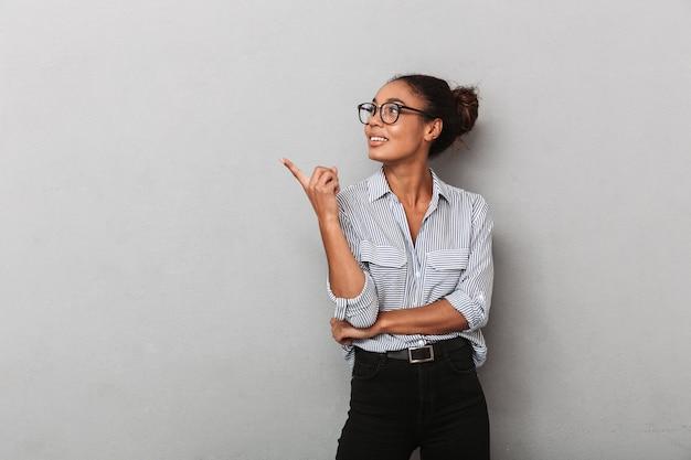Mulher de negócios na áfrica confiante usando óculos e camisa em pé, isolada sobre o cinza, apontando para longe