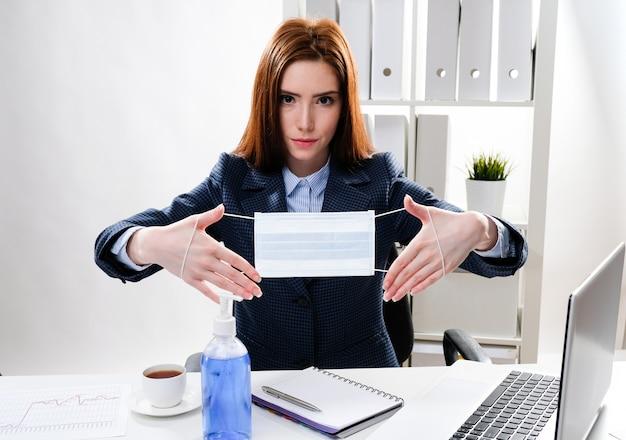 Mulher de negócios na mesa com um computador tem uma máscara médica nas mãos dela