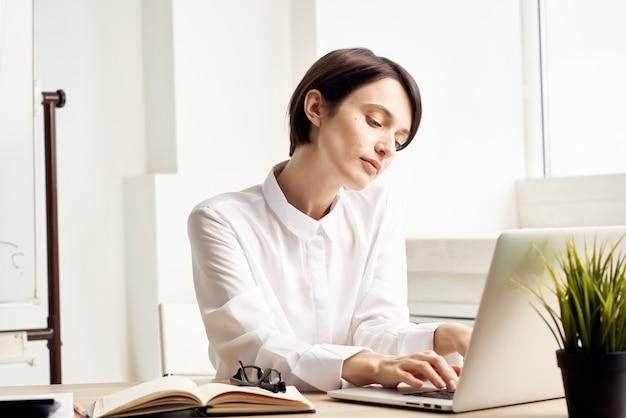 Mulher de negócios na mesa de trabalho em frente à emoção de tecnologia de laptop