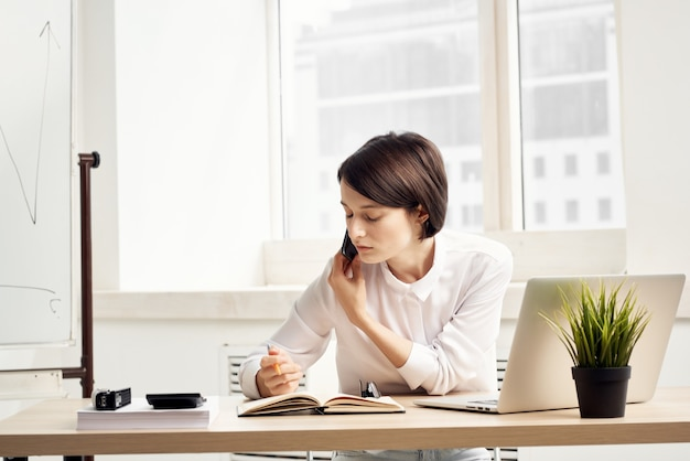 Mulher de negócios na mesa documenta um plano de fundo claro de trabalho profissional