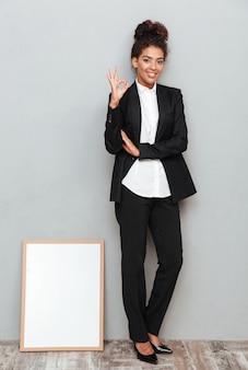 Mulher de negócios na parede cinza