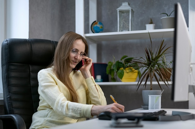 Mulher de negócios na poltrona de couro assina documentos. o contador trabalha com relatórios. mulher de negócios bem-sucedida.