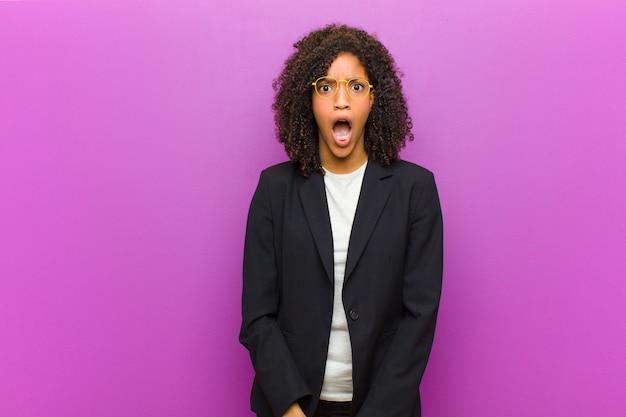 Mulher de negócios negra jovem se sentindo aterrorizada e chocada com a boca aberta em surpresa