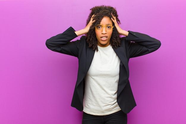 Mulher de negócios negra jovem se sentindo horrorizada e chocada, levantando as mãos na cabeça e entrando em pânico por um erro