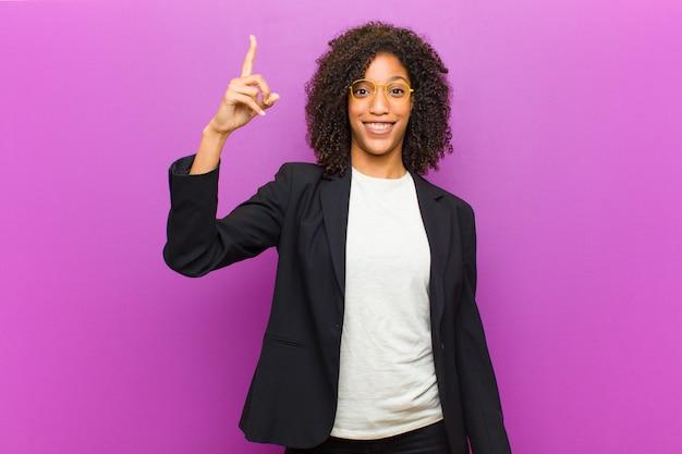 Mulher de negócios negra jovem se sentindo um gênio feliz e animado depois de realizar uma idéia, alegremente levantando o dedo, eureka!